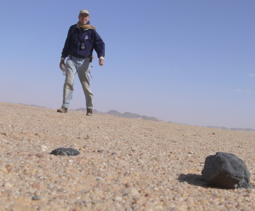 A photograph of a man walking towards a meteorite in Sudan's Nubian Desert.
