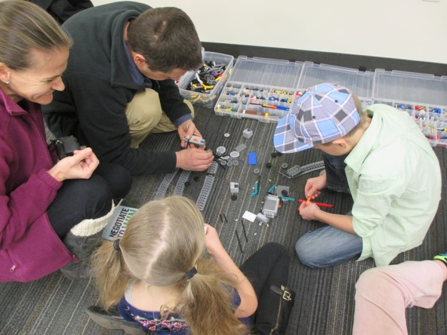 A photo of two children and two adults working with small wheels and blocks