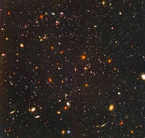a photo taken by the Hubble Space Telescope of thousands of small galaxies of all different shapes and colors.