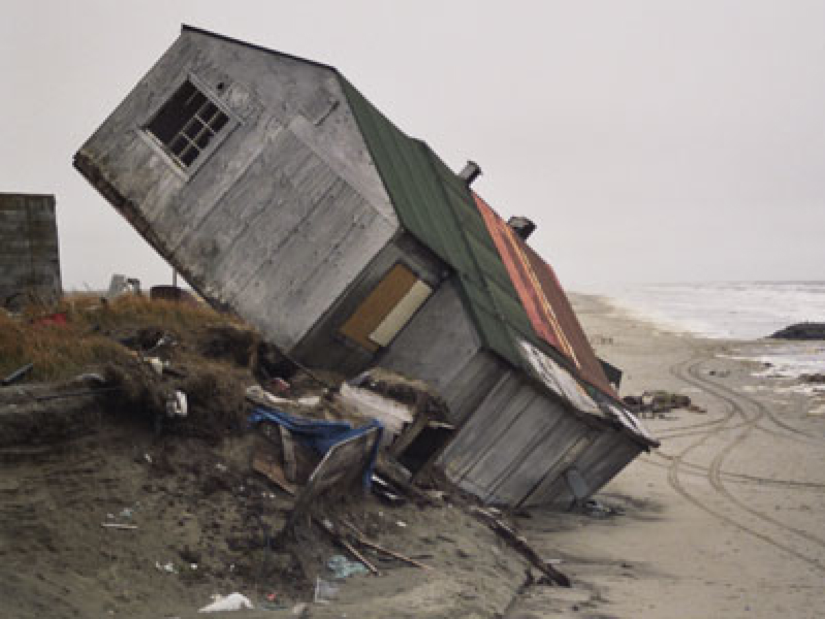 Photo of beach house tipped at a 45-degree angle, resting on a sand dune.