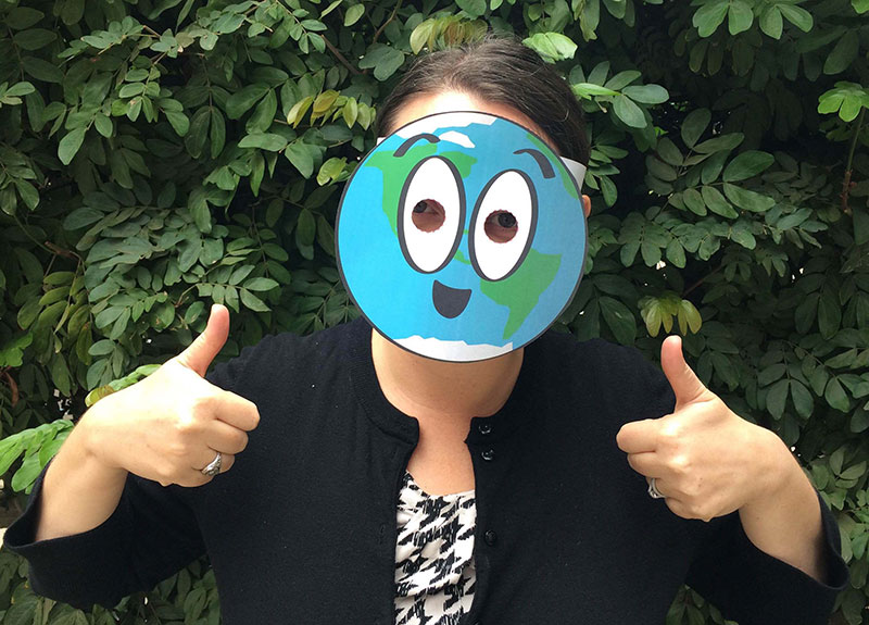 a person wearing a cartoon paper mask of the Earth