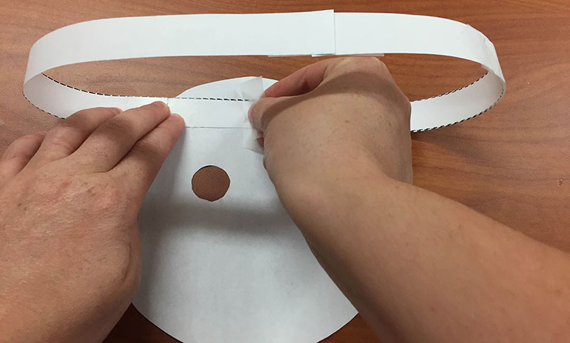 a person tapes a paper ring to the back side of a planet mask cutout