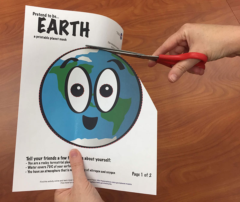 a photo of scissors cutting a cartoon of Earth out of a piece of paper