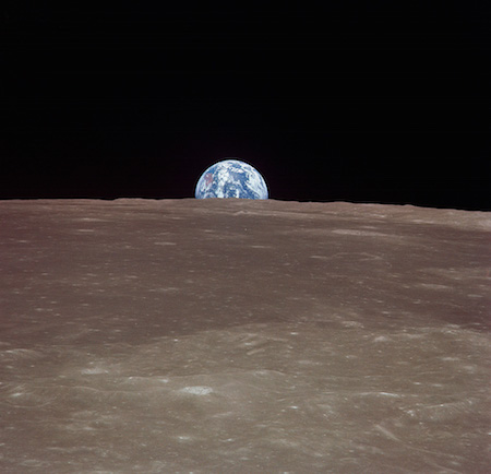 Fotografía de la Tierra en el fondo, de aspecto muy pequeño. La superficie de la luna está en primer plano, entonces la Tierra asciende por encima de la luna.