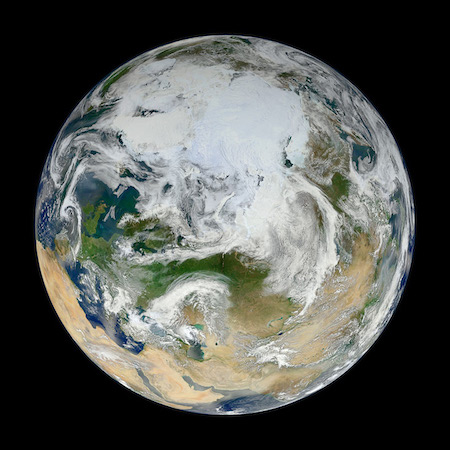 A photo of the northern portion of the Earth. Swirls of white cover it.