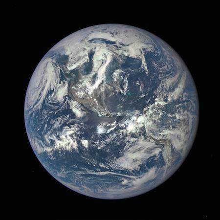 Fotografía de la Tierra en la que se ven América del Norte y del Sur, los océanos y unos remolinos de nubes.