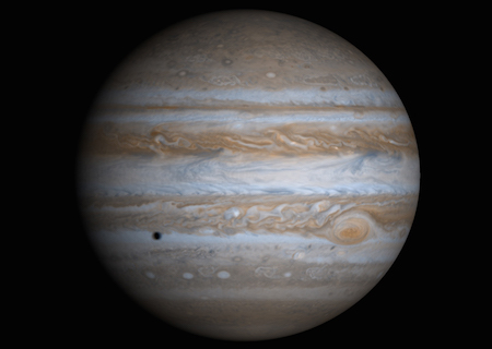 A full face of Jupiter with the Great Red Spot on the right hand side. A small dark spot on the left side of Jupiter is the shadow of a moon passing in front.
