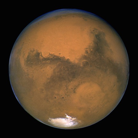 A photo of one full lit side of Mars, showing the reddish brown color of its surface and a white spot on the southern side.