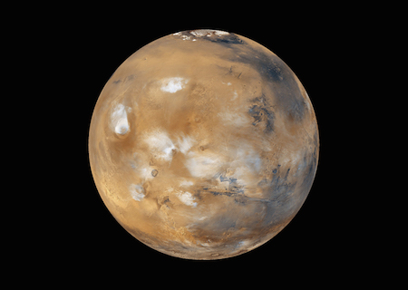 A photo of one full lit side of Mars showing several white splotches that are water-ice clouds and ice on the ground.