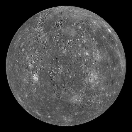 A photo of one whole lit side of Mercury. It has craters and lightly colored splotches.