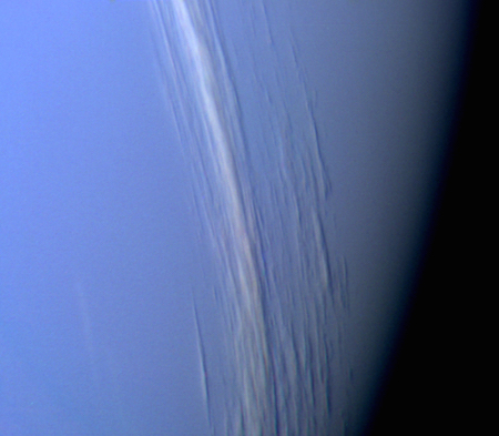 A close up photo of Neptune where it appears a light purple and long white clouds stretch across it.