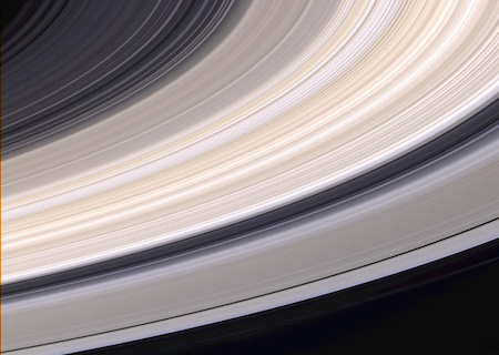 A close up view of Saturn's rings. They are grey and tan, and there are spaces in between where you can see the black color of space through them.