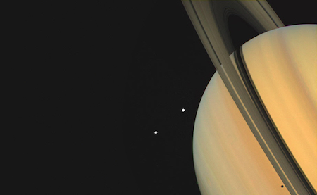 A photo of Saturn with its rings at an angle pointing upwards. Next to Saturn are two white dots, which are moons.