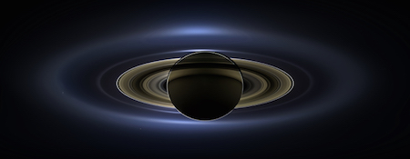 A photo of Saturn where it is backlit by the sun. Saturn and its rings are nearly black, and the sun is making the edges glow.