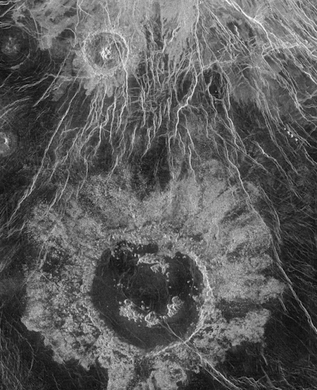 a photo of a large crater and lots of white cracks in the surface