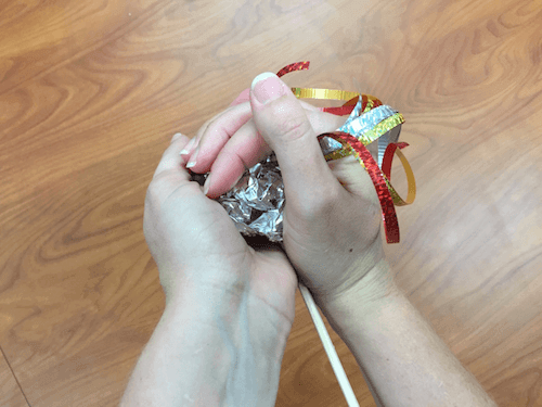 a photo of hands cupping the tin foil together into a ball