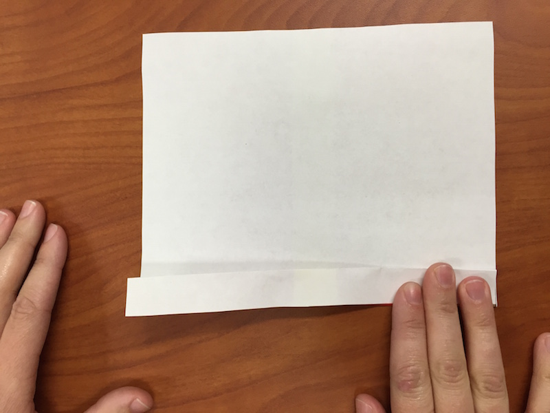 a photo of the paper turned over so the white side is facing up, and hands making the second fan fold
