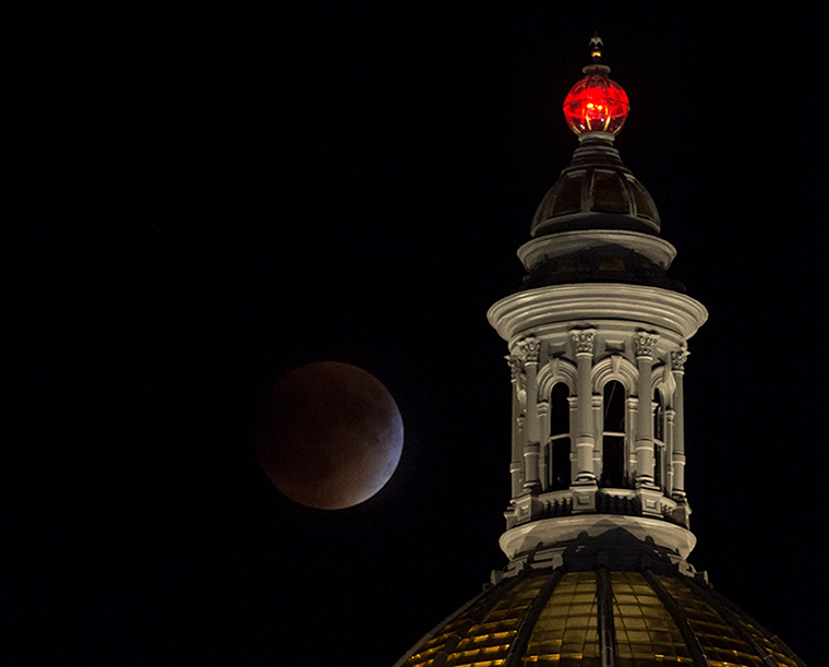 Image of a supermoon total lunar eclipse behind the Colorado State Capitol building.
