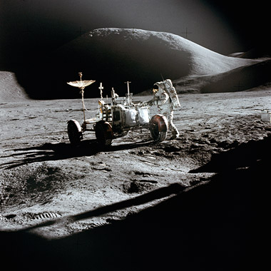 Photo of astronaut and lunar rover on the Moon, with hills in the background.