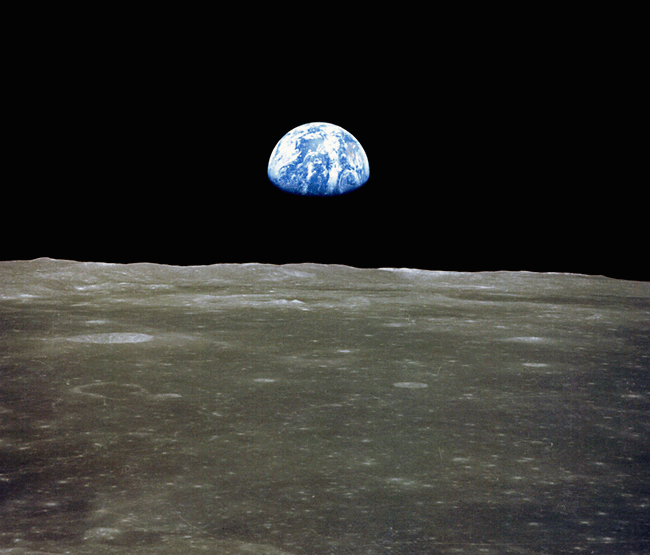 View across lunar landscape, with distant Earth, top half lit, rising above the horizon.