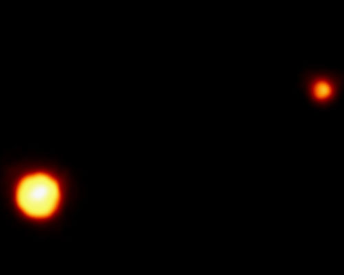 Pluto appears as a bright orange spot in the lower left and Charon as a smaller orange dot in the upper right.