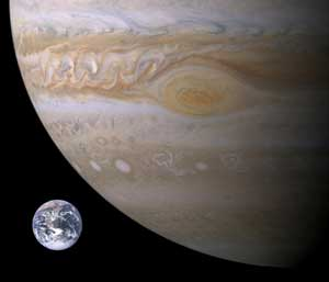 Photographic images of about one-quarter of Jupiter and full Earth side by side, to scale. Earth is tiny.
