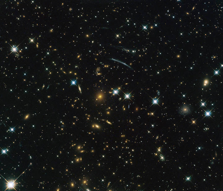 An image of hundreds of small galaxies on the black background of space.