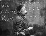 Photo of Einstein in front of chalk board with equations written on it.