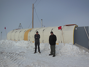 Panorama of McMurdo station on the left and expanse of snow for the right three-quarters of the image.