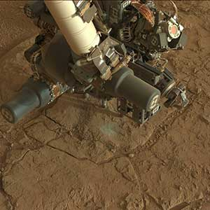Image of Curiosity's robotic arm with tools on it close tot he Martian ground. Lots of fine red dust on the tools.