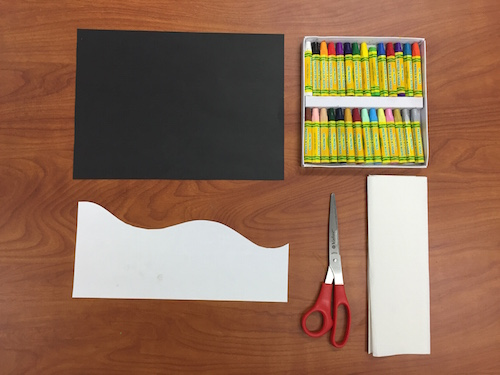 a photo of a table with a black piece of construction paper, a set of oil pastels, a piece of paper cut with a wave shape, scissors, and a paper towel.