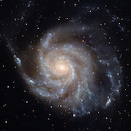 picture of the pinwheel galaxy with visible light so the pinwheel shape appears in tans, purples, and greys.