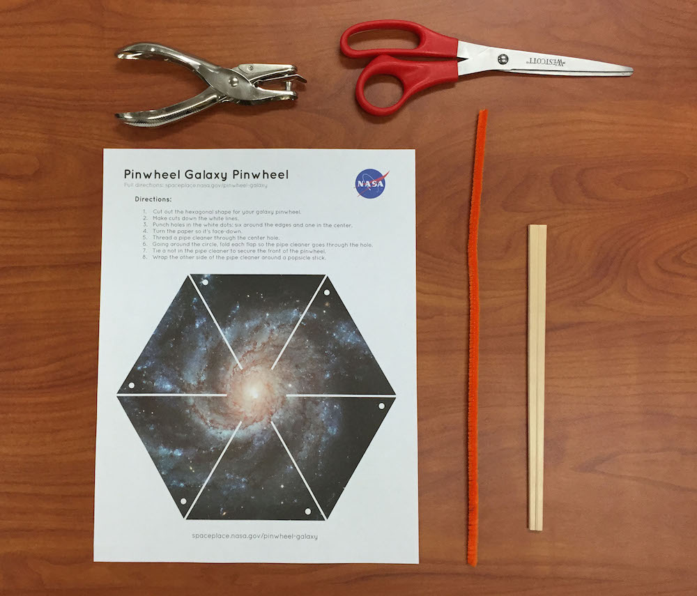 a photo of the supplies needed for this activity: the pinwheel galaxy printout, scissors, single hole puncher, a pipecleaner, and chopsticks.