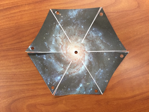 The cut out hexagonal shape of the pinwheel galaxy printout with one cut down the side along the line.