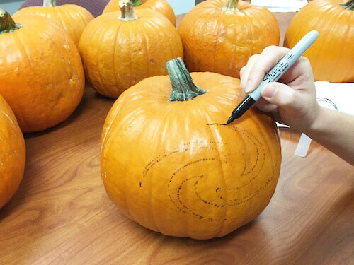 a marker is used to trace the shape of a galaxy on a pumpkin
