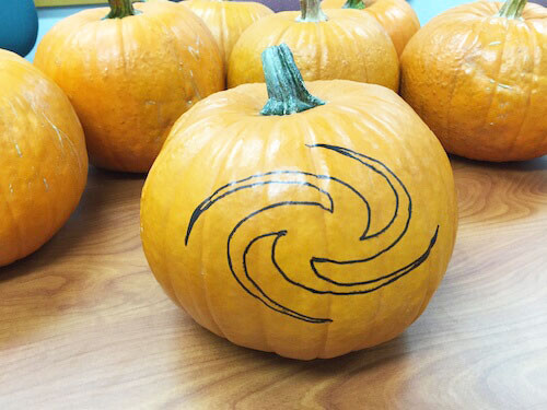 an outline of a galaxy shape on a pumpkin