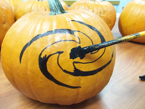 a paintbrush with black paint is being used to fill in the galaxy shape on a pumpkin