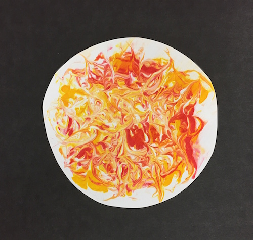 the cut out sun shape with swirls of food coloring mounted on a black piece of paper