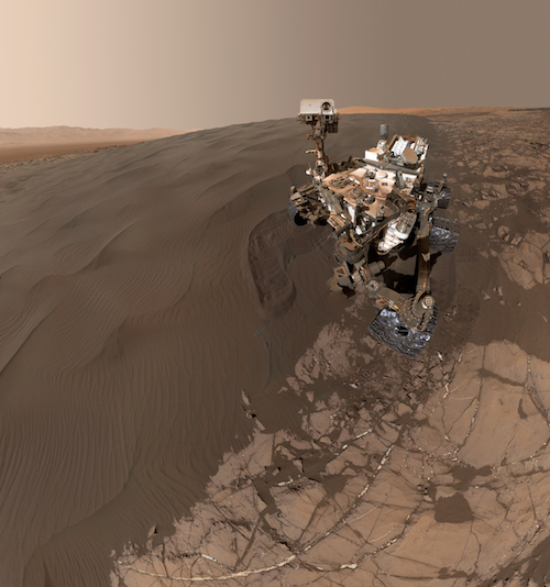 An image of the Curiosity rover taking a self-portrait on a Martian sand dune.