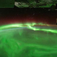 a photograph of green auroras over the Earth