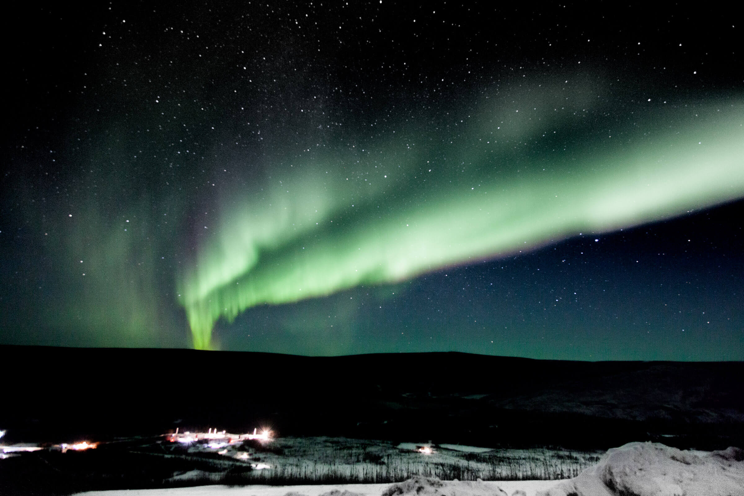 A photograph of green aurora against a dark night sky
