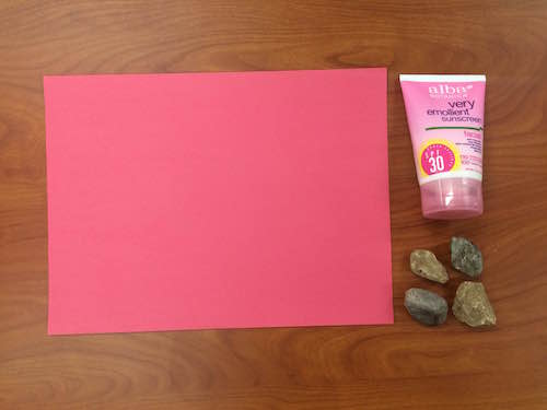a photo of construction paper, sunscreen, and rocks on a table top