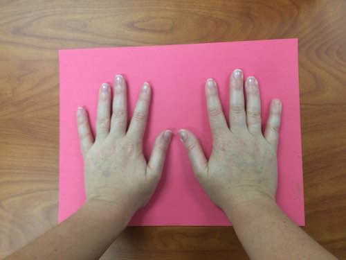 hands placed palm-side-down on a piece of red construction paper
