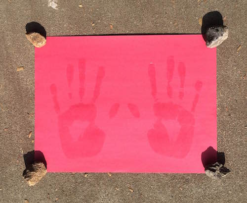 construction paper with wet sunscreen handprints placed in the sun with small rocks on the four corners of the paper