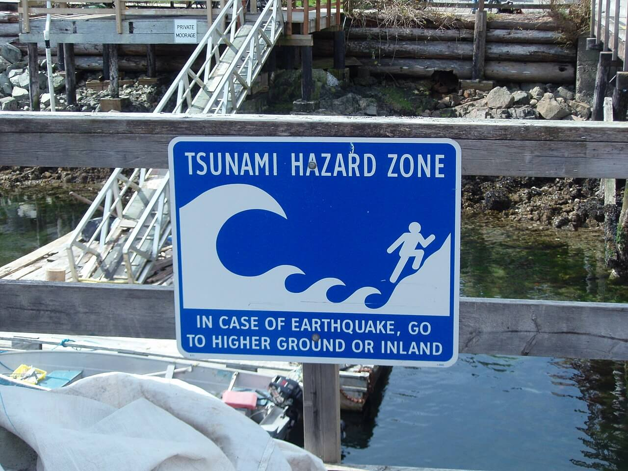 Tsunami warning sign that reads TSUNAMI HAZARD ZONE IN CASE OF EARTHQUAKE, GO TO HIGHER GROUND OR INLAND.