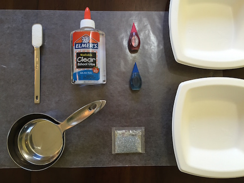 a photo of a teaspoon of borax, school glue, red and blue food coloring, glitter, measuring cups, two bowls, and wax paper on a table top