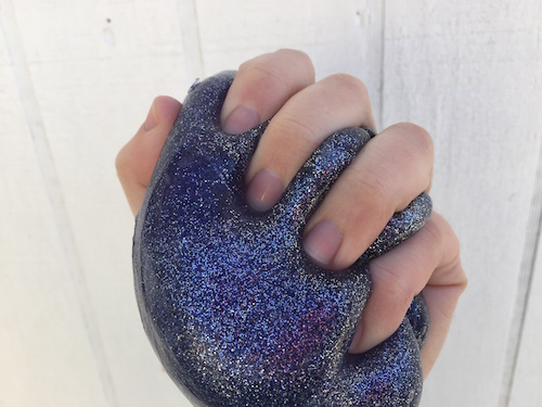 an image of a hand holding purple universe slime with lots of glitter